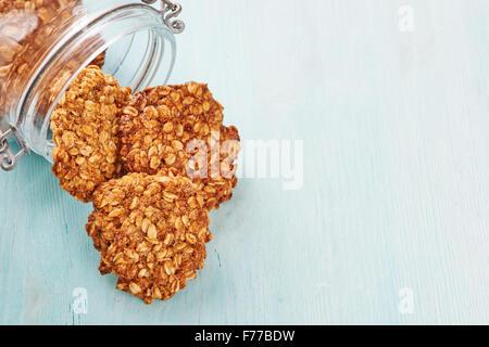 Homemade oatmeal banana cookies, jar and blu wooden table - Stock Photo