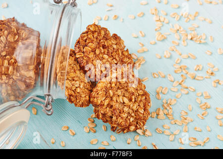 Homemade oatmeal banana cookies, surrounded by oatmeal, jar and blu wooden table - Stock Photo