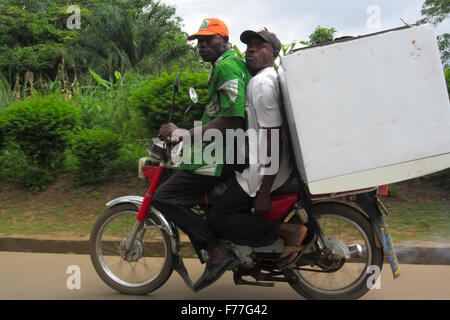 Two friends riding a motorbike, transporting a fridge in Nigeria - Stock Photo