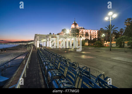 Hotel Negresco on Promenade des Anglais in Nice, blue chairs in a row,  twilight, Provence-Alpes-Cote d'Azur, France - Stock Photo