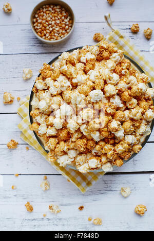 Big bowl of popcorn on white rustic background with corn seeds - Stock Photo