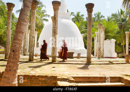 Sri Lanka - Mihintale Temple, monks in front of the stupa, Ambasthale Dagoba, UNESCO - Stock Photo