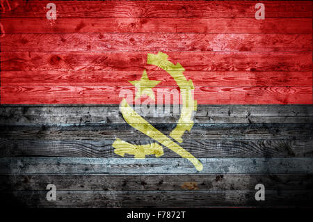 A vignetted background image of the flag of Angola painted onto wooden boards of a wall or floor. - Stock Photo