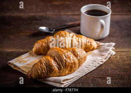 Breakfast with fresh baked croissants and coffee on wooden background - Stock Photo