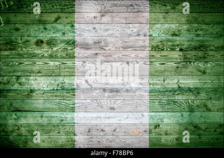 A vignetted background image of the flag of Nigeria onto wooden boards of a wall or floor. - Stock Photo