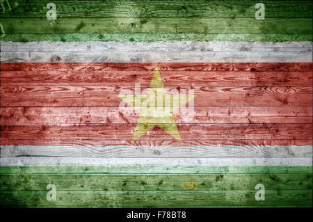 A vignetted background image of the flag of Suriname onto wooden boards of a wall or floor. - Stock Photo