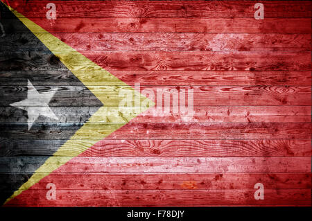 A vignetted background image of the flag of Timor Leste onto wooden boards of a wall or floor. - Stock Photo