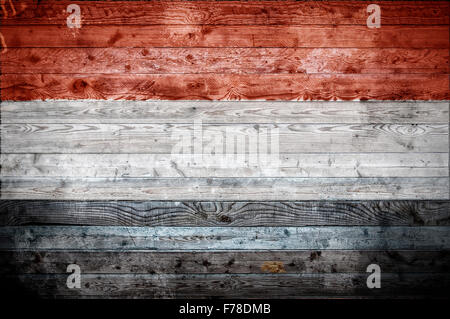 A vignetted background image of the flag of Yemen onto wooden boards of a wall or floor. - Stock Photo