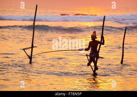 Tropical sea landscape with stilt fisherman at sunset time, Koggala Beach, Sri Lanka, Asia