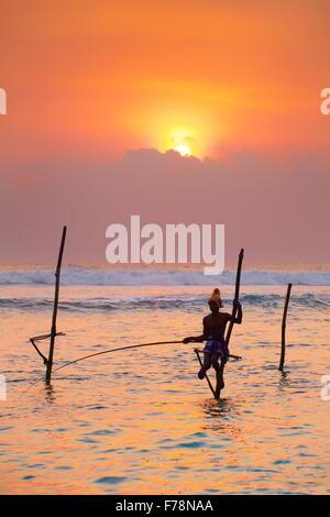 Sri Lanka - stilt fisherman fishing in the sea, tropical sunset at Koggala Beach, Asia - Stock Photo