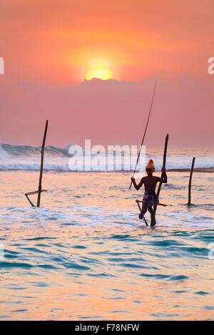 Local stilt fisherman at sunset, Koggala Beach, Sri Lanka, Asia