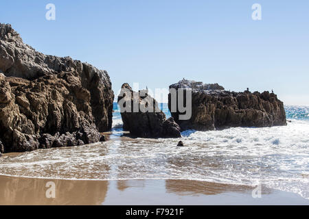 Rock formations at Leo Carrillo Beach State Park in Malibu California during the summer at low tide. - Stock Photo