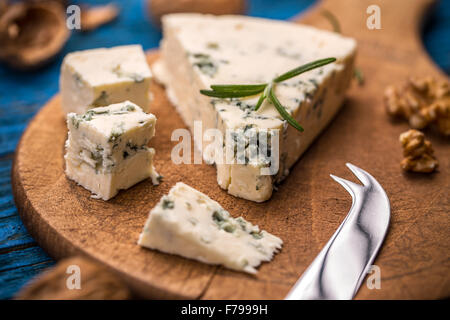 Slices of danish blue cheese on wooden cutting board - Stock Photo
