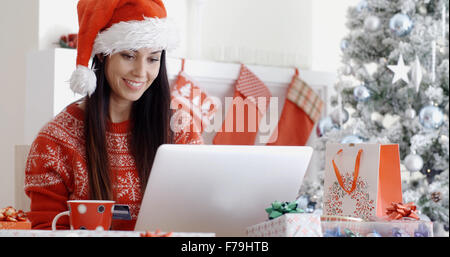 Smiling woman doing online Christmas shopping - Stock Photo