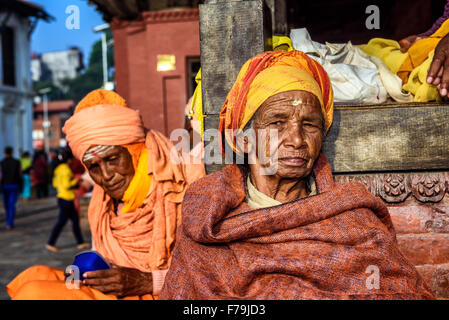 Old woman begging at Pashupatinath Temple complex in Kathmandu - Stock Photo
