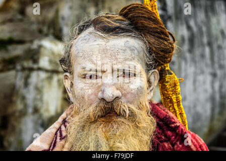 Portrait of wandering  Shaiva sadhu (holy man) with traditional face painting in ancient Pashupatinath Temple - Stock Photo