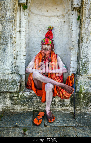 Wandering  Shaiva sadhu (holy man) with traditional face painting in ancient Pashupatinath Temple - Stock Photo