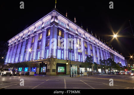 Selfridges Department Store in Oxford Street illuminated at night with people passing, central London - Stock Photo