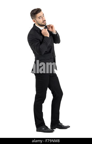 Side view of cool elegant young male model adjusting bow tie looking at camera. Full body length portrait isolated - Stock Photo