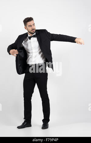 Young man putting on black suit tuxedo coat. Full body length portrait over gray studio background - Stock Photo