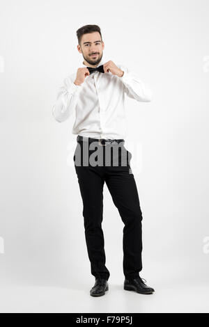 Smiling young groom adjusting bow tie looking at camera. Full body length portrait over gray studio background. - Stock Photo