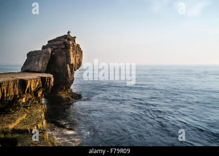 Rocky cliff landscape with sunset over ocean with unidentified people on cliff top - Stock Photo
