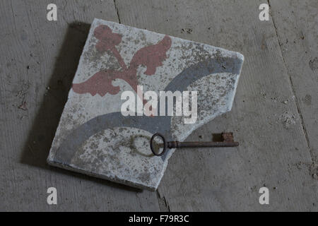 Colored broken ceramic tile and the rusty key of the main building entrance, hosting M. Papamalis wallpaintings. - Stock Photo