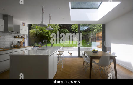 Dining Room and Kitchen in UK home with view through patio doors to garden - Stock Photo