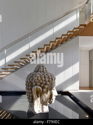 Buddha head statue in the stairwell of a house in Cove Way, Sentosa, Singapore designed by Robert Greg Shand Architects - Stock Photo