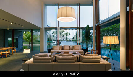Lit double height living room in a family house in Cove Way, Sentosa, Singapore designed by Robert Greg Shand Architects - Stock Photo