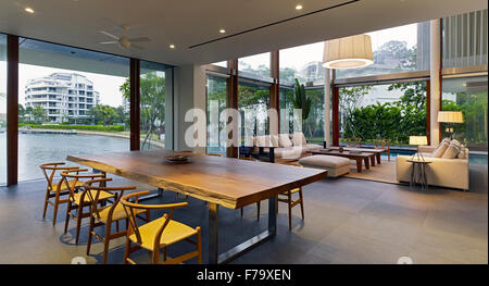 Interior open plan living and dining area, room in a house in Cove Way, Sentosa, Singapore designed by Robert Greg - Stock Photo