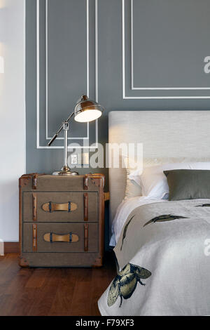 Master suite with classic antique travel trunk by a large bed in a house in Cove Way, Sentosa, Singapore designed - Stock Photo