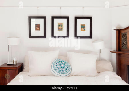 Double bed and artwork with cushions in Sydney home of designer and Heritage Consultant Janine Hendry. - Stock Photo