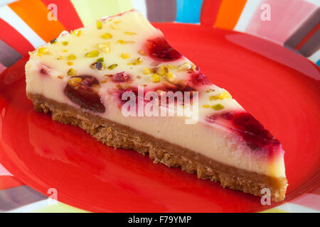 Tesco finest Raspberry & Pistachio cheesecake slice on red colourful plate - Stock Photo