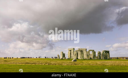Stonehenge, prehistoric monument, set against the groups of visitors and a blue sunny sky. - Stock Photo