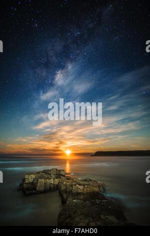 Moonrise beneath the milky way - Stock Photo