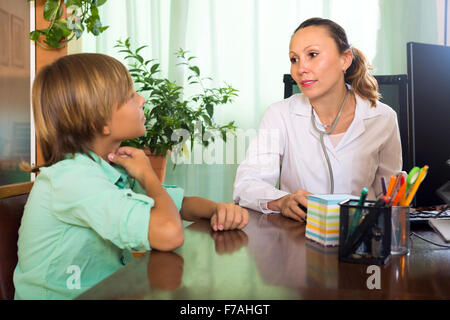 Friendly female doctor examining throat of teenage boy in clinic. Focus on woman - Stock Photo
