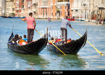 Tourists in venetian gondolas on Grand Canal (Canal Grande), Venice, Italy - Stock Photo