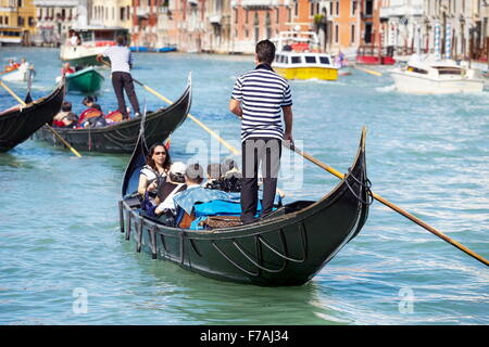 Venetian Grand Canal (Canal Grande) - tourists in gondola exploring Venice, Italy - Stock Photo