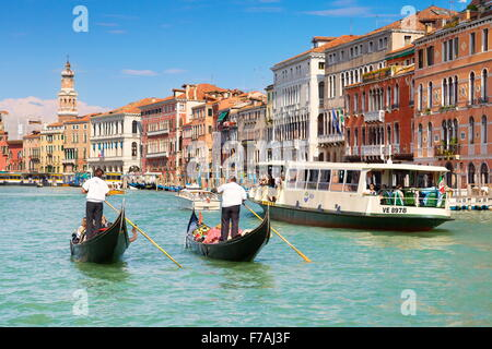 Two venetian gondolas and waterbus on Grand Canal (Canal Grande) - Venice, Italy - Stock Photo