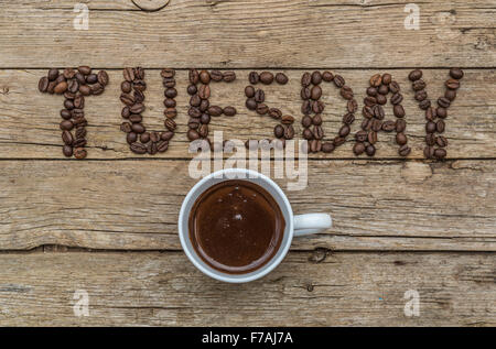 Cup of coffee on wooden background and TUESDAY coffee beans - Stock Photo