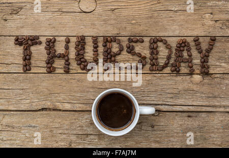 Cup of coffee on wooden background and THURSDAY coffee beans - Stock Photo