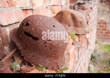 two old rusty military helmets near the brick wall - Stock Photo