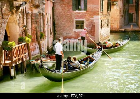 Venice - Gondolier sailing his Gondola on the canal Venice, Veneto, Italy - Stock Photo