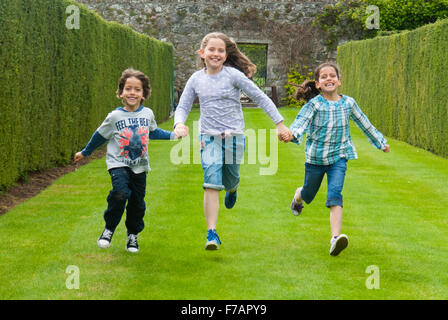 Three children running along the grass at the Rose Gardens at Drum Castle in Aberdeenshire, Scotland. - Stock Photo