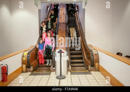 New York, USA. 27th November, 2015. Shoppers ride the vintage wooden escalators in the Macy's Herald Square flagship - Stock Photo