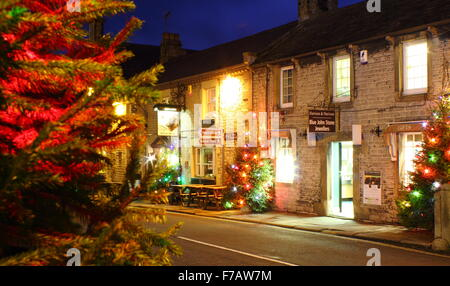Christmas trees strung with fairy lights line the main street in Castleton, a pretty village in Derbyshire's Peak - Stock Photo