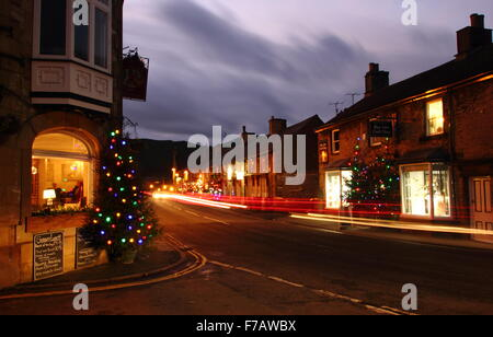 Christmas trees strung with fairy lights line the main street in Castleton, a pretty village in the Peak District, - Stock Photo