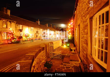 Christmas trees strung with fairy lights decorate the main street in Castleton, a village in the Hope Valley, Peak - Stock Photo