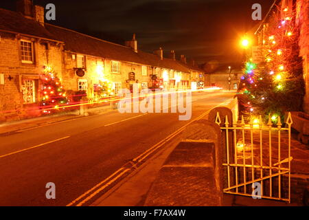 Decorated Christmas streets light up the main street in Castleton, a pretty village in the Peak District National - Stock Photo